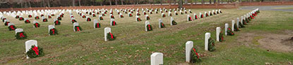 Pine wreaths decorate rows of headstones.