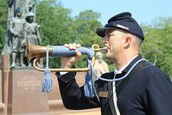 A volunteer in Union uniform blows Taps
