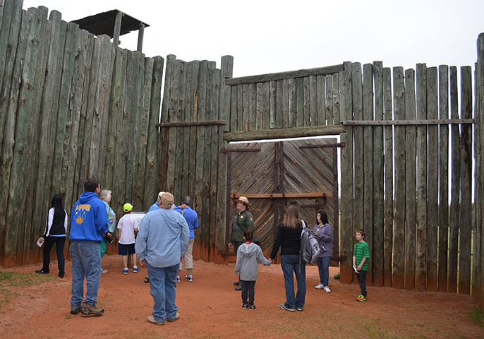Park ranger and visitors stand inside wooden stockade gate