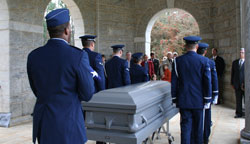 Uniformed soldiers stand around a casket
