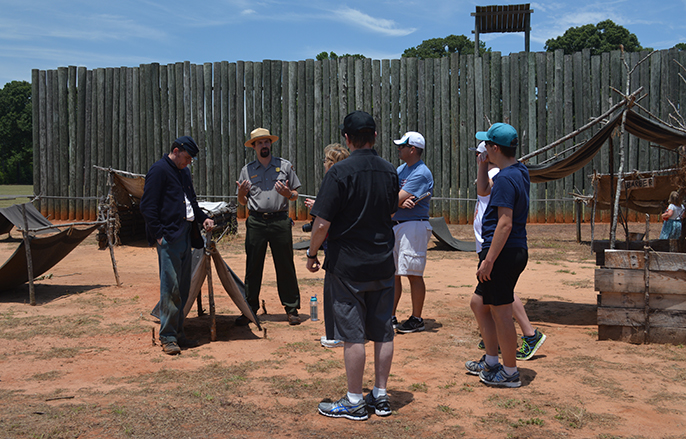 Living historian and park ranger talk to visitors in the prison site