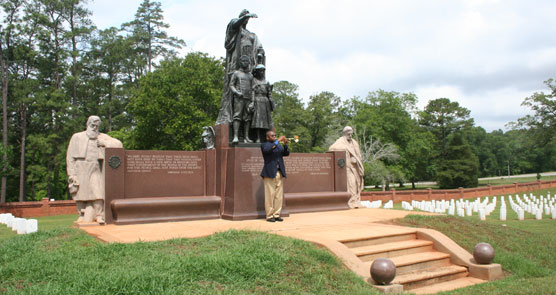 Young man blowing Taps on a bugle below a bronze and stone statue