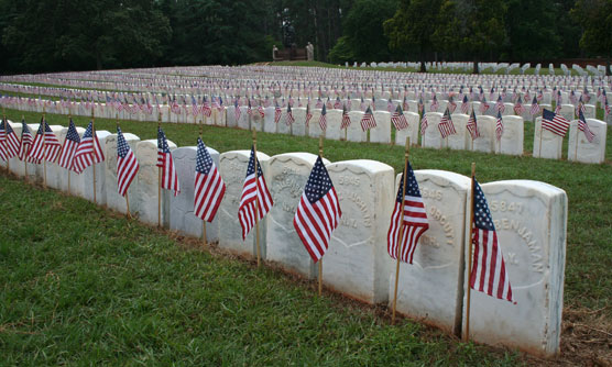 American flags in front of graves in the National Cemetery