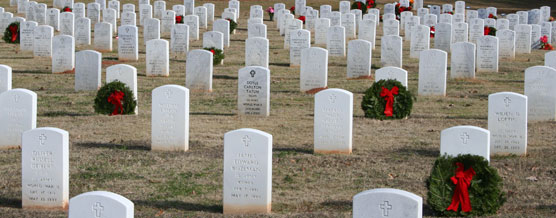 Holiday wreaths decorate rows of white headstones