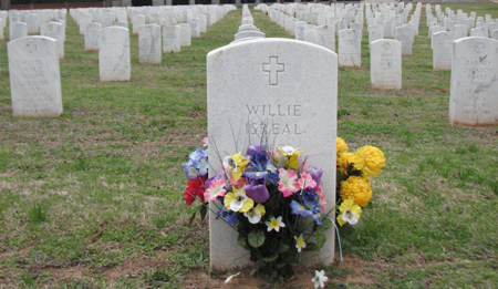 Artificial flowers in front of a white headstone