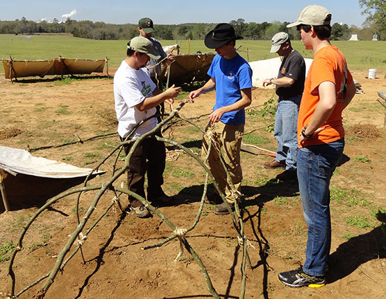 Staff and volunteers construct a shelter with branches.