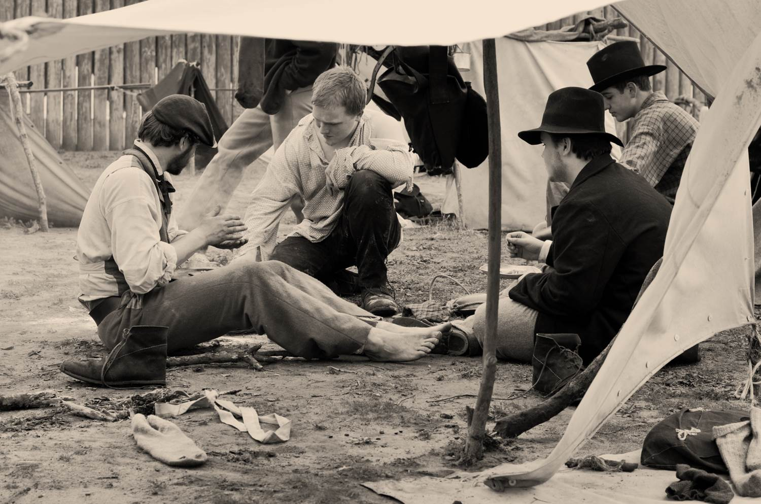 Four men in ragged Civil War era clothes sit on the ground under a makeshift shelter.