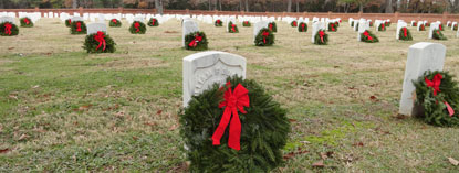 Wreaths distributed among white headstones.