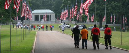 Men walk down a cemetery avenue lined with American flags