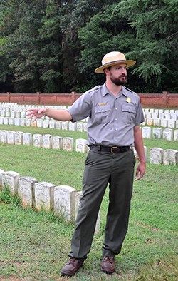 Park ranger stand near large number of Civil War graves