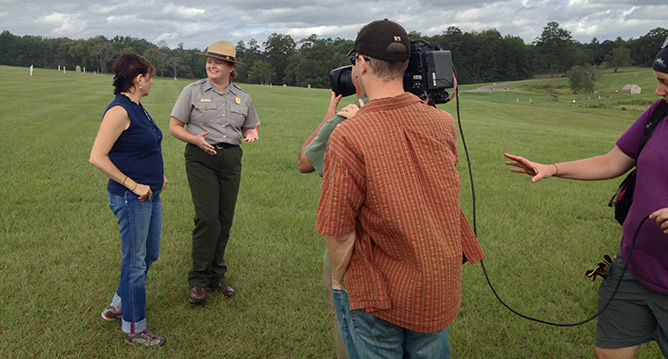 Park ranger works with a camera crew