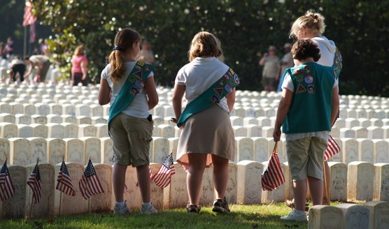 A group of Girl Scouts place flags on graves in the Andersonville National Cemetery.