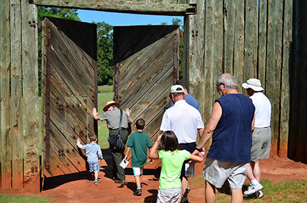 A park ranger leads a group through the reconstructed north gate of the prison.