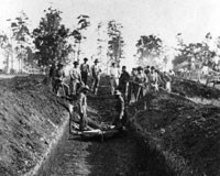 Men standing in a waist-deep burial trench