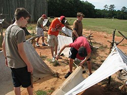 Boy scouts work to assemble canvas shelters