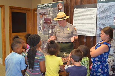 A uniformed park ranger speaks with children