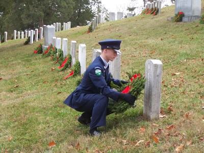 High School ROTC student lays wreath on grave of fallen hero