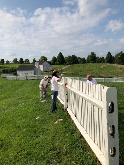 Volunteers painting a fence on the battlefield.