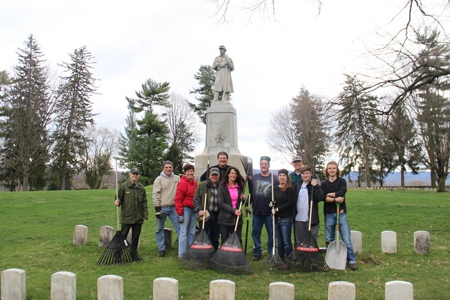 Group shot of volunteers in the National Cemetery holding tools.