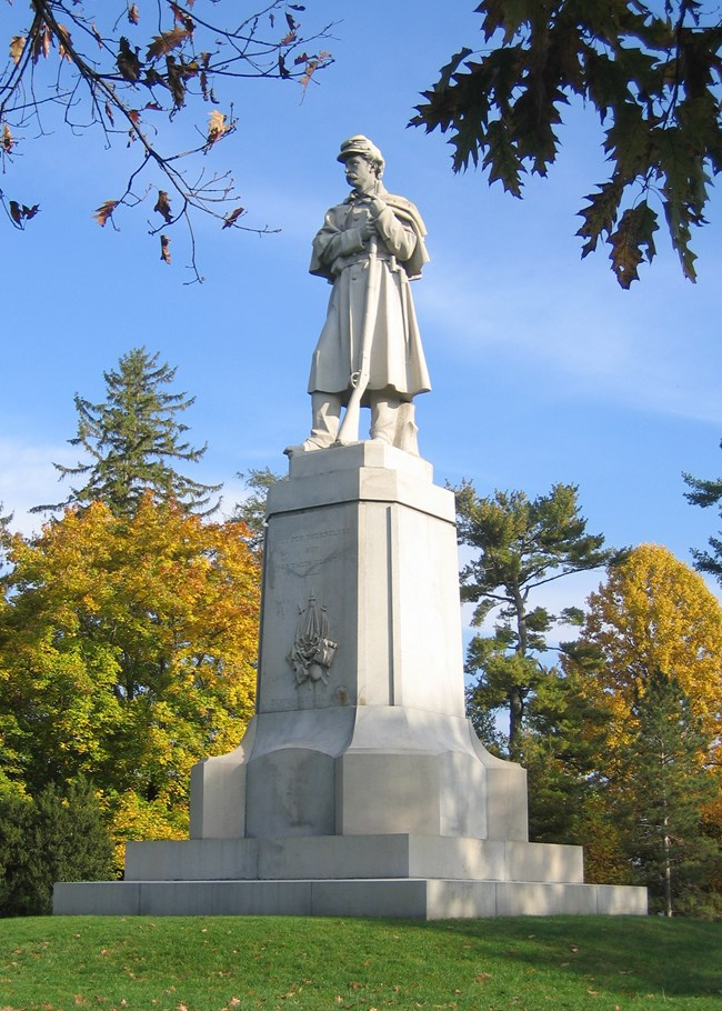 A stone statue of a Civil War soldier leaning on a rifle atop a stone plinth.