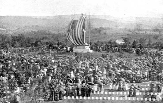 Black and white photo of a large crowd gathered in a field around the Private Soldier Statue. A huge US flag is draped over the statue and is blowing in the breeze.