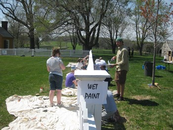 Volunteers painting white picket fences in the village.