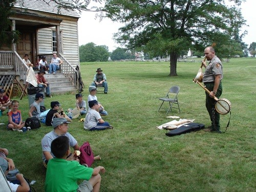 Ranger David Wooldridge demonstrates the banjo and discusses its significance to Appomattox Court House and the cultural exchange involved.