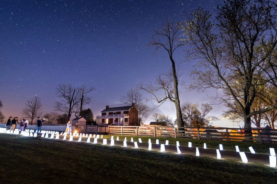 white luminaries light up the brick McLean house and add glow to the dirt road under a deep blue sky