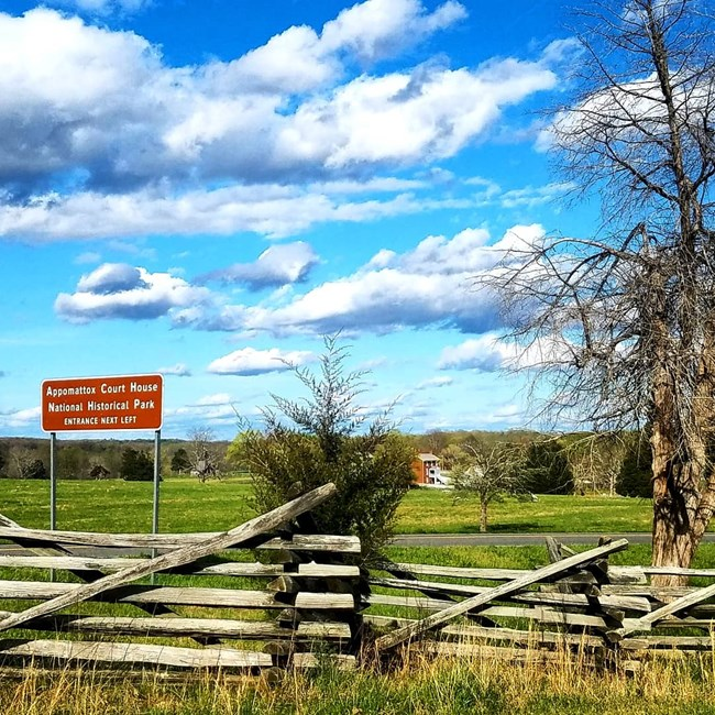 A split-rail fence in the foreground with the brown directional sign for Appomattox Court House above and to the left against a deep blue sky with fluffy white clouds. The reconstructed brick McLean House is just visible on the far ridgeline.