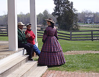 An actress portraying Mrs. George Peers converses with park visitors.