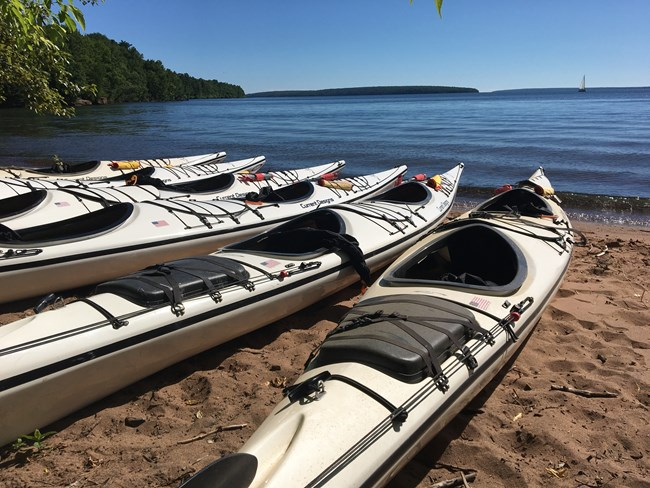6 Tandem White Sea Kayaks sitting on beach at water's edge with islands in the background.