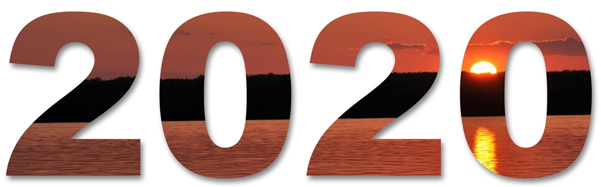 An image of sunset over a wooded island, reflected in the water, within the number 2020.