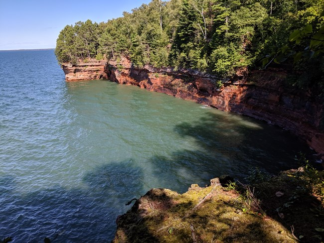 Tree-covered red cliffs meet greenish blue water, in a bowl shape.