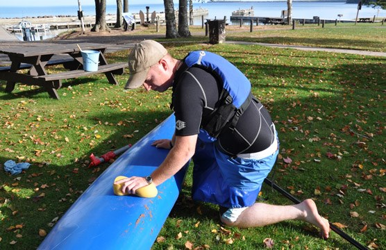 Kayaker cleaning his boat of invasives