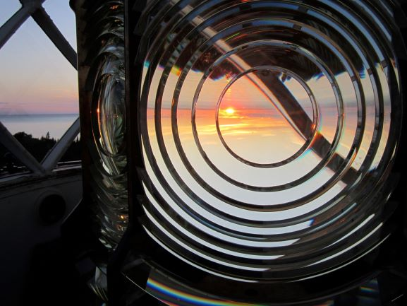 Sunset through a fresnel lens looking over a body of water
