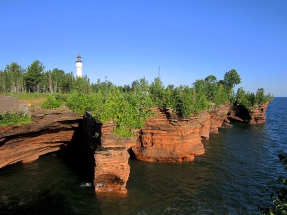 Sandstone cliffs on lake shore with trees and white lighthouse tower on top of cliffs.