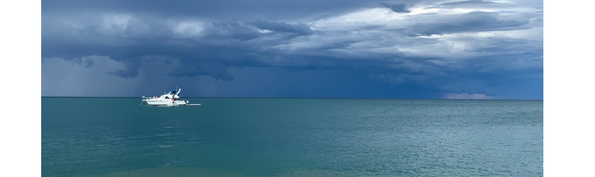 A white boat surrounded by water with dark clouds above.