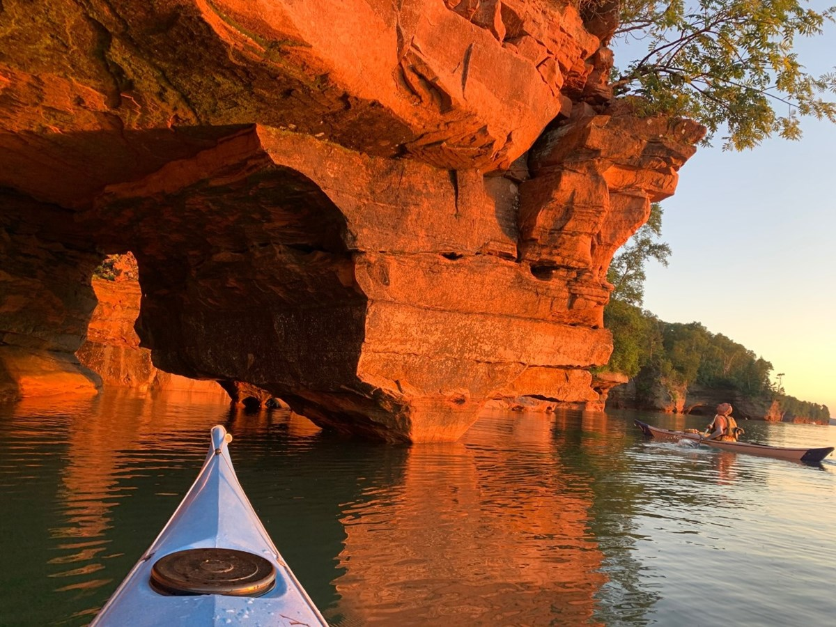 Two kayakers on the lake looking at a sandstone arch.