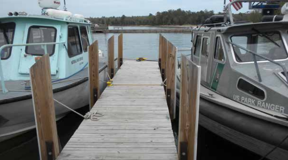 A wooden dock with two boats tied on either side.