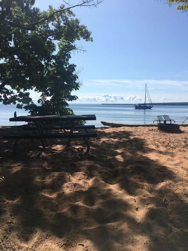 A shaded picnic table in the sand looking out at a lake with an anchored sailboat.