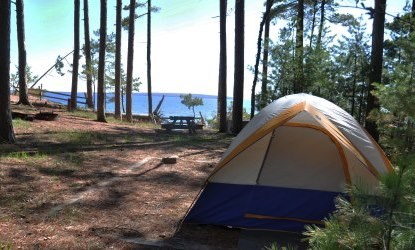 Tent on the tent pad at campsite twelve on Stockton Island, with Lake Superior in the background.