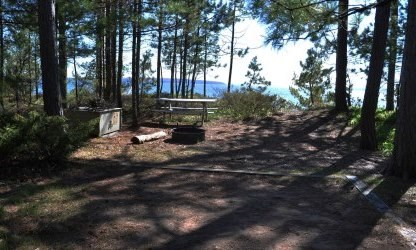 Tent pad shaded by white pine trees, with bear locker and picnic table in the background, overlooking Lake Superior.