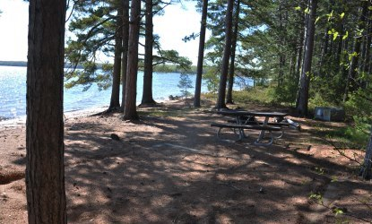 Tent pad, bear locker, and picnic table at campsite nineteen on Stockton Island, next to the beach on Lake Superior.