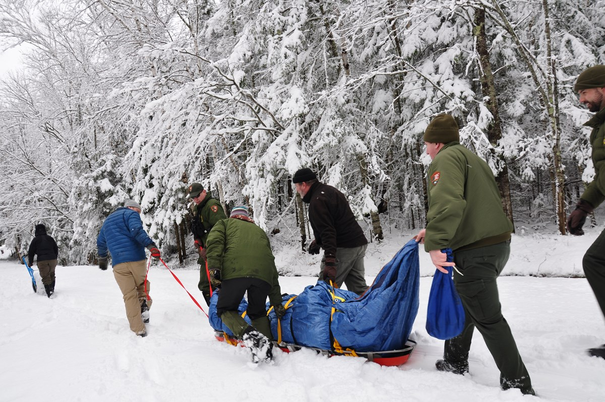 6 park rangers pull a patient wrapped in a tarp on a sled in the snow.