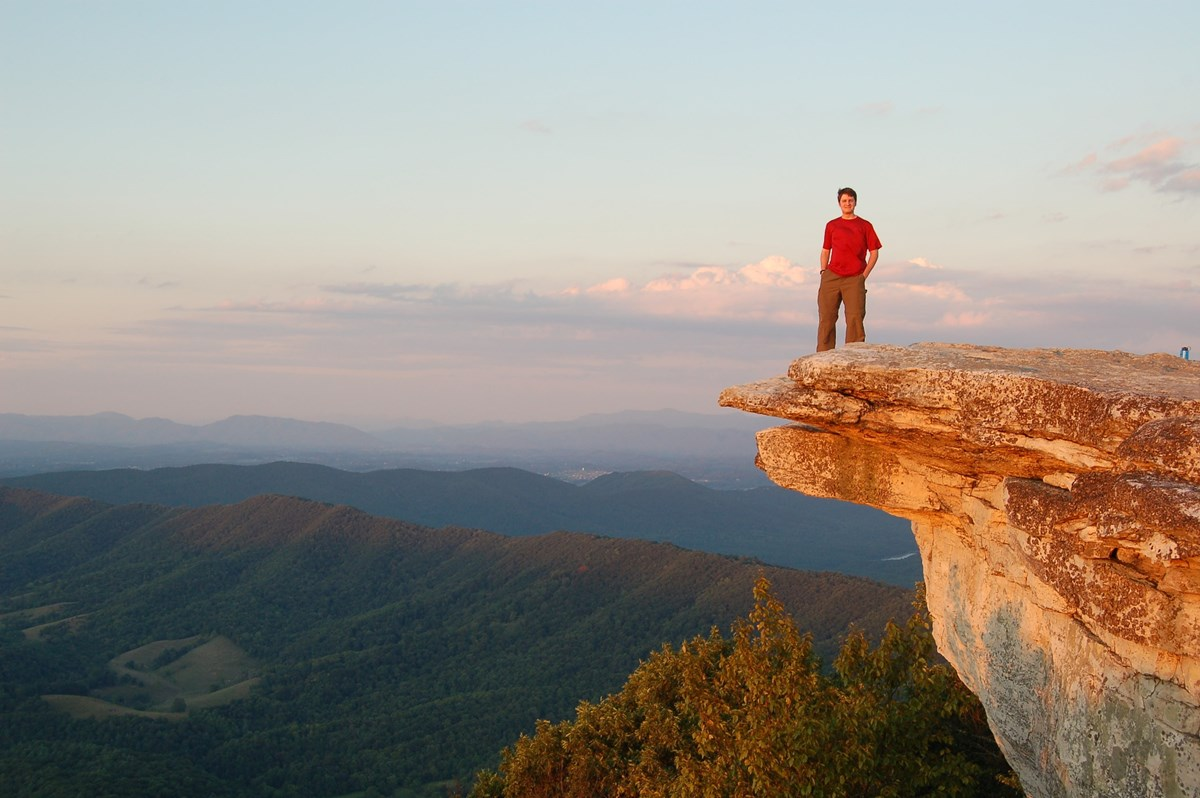 Man stands on McAfee Knob overlooking mountains.