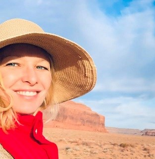 blond woman in sunhat, red vest, blue sky and redrock behind