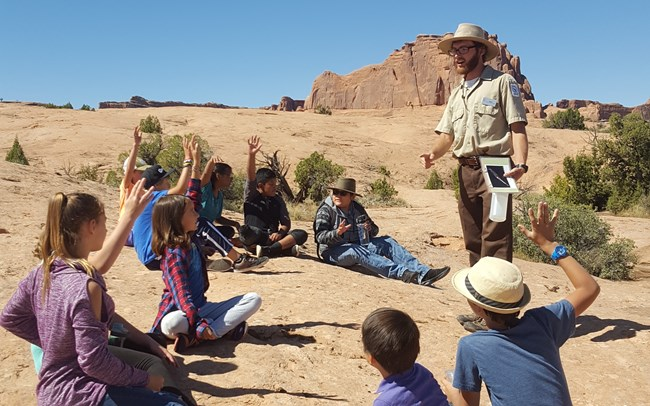 Education volunteer addresses school group seated on slickrock