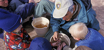 A volunteer and children look over a bucket filled with soil