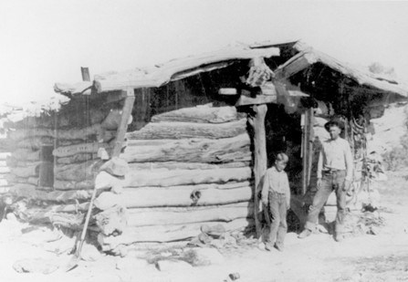 A man and a boy stand in the door of a cabin.