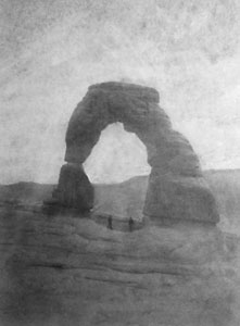 a black and white image shows Delicate Arch with two people standing beneath it